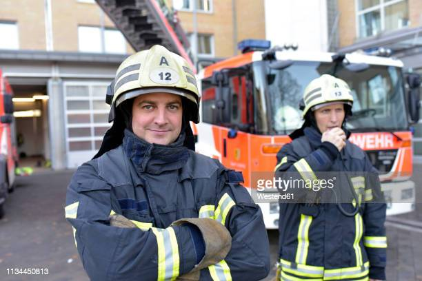 portrait of two confident firefighters in front of fire engine - bombero fotografías e imágenes de stock