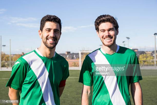 portrait of two confident football players on football field - camiseta deportiva fotografías e imágenes de stock