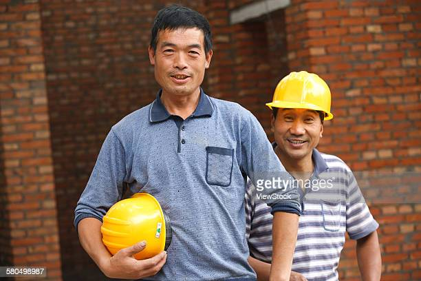 portrait of two construction workers  - migrant worker stock pictures, royalty-free photos & images