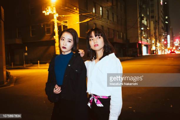 Portrait of two contemporary young Japanese woman at night street.