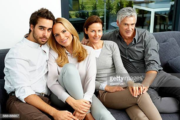 Portrait of two couples sitting together on a couch