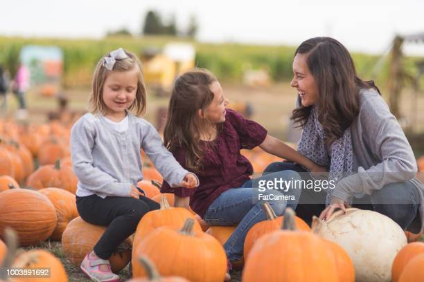 Portrait of two cute girls and their mom at pumpkin patch