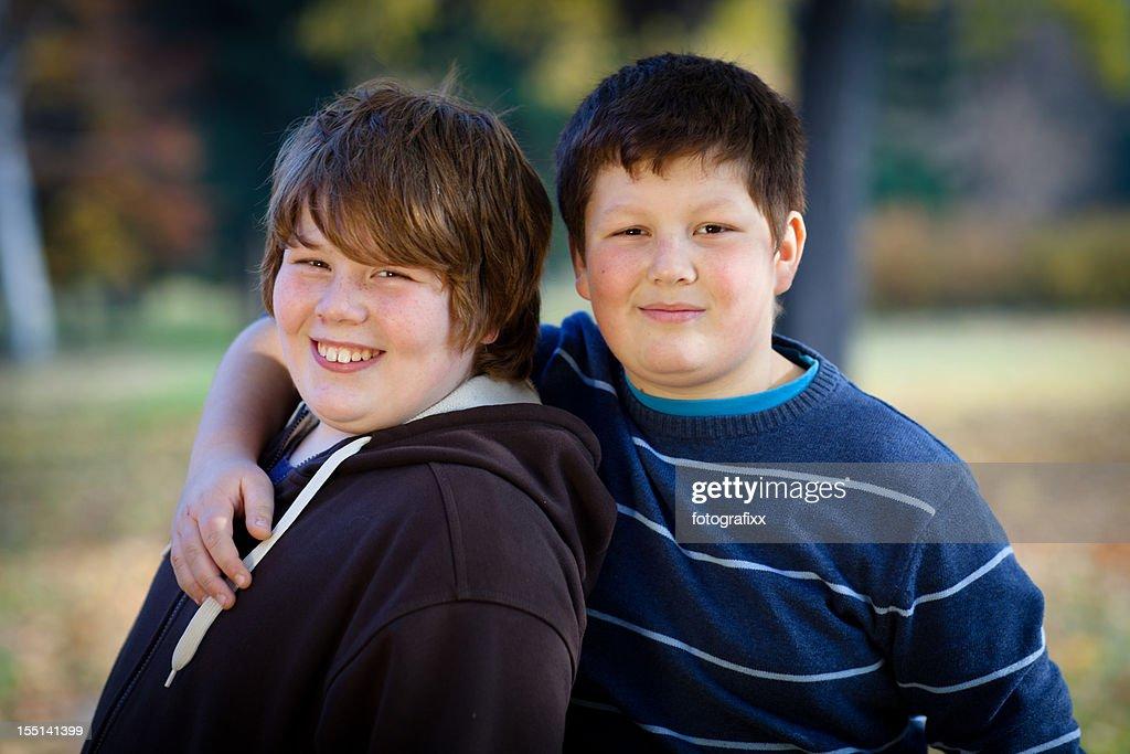 Retrato de dois lindos meninos, braços em torno de excesso de peso : Foto de stock