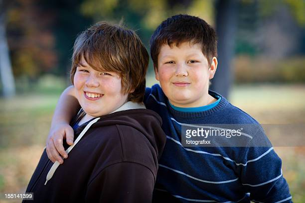 portrait of two cute overweight boys, arms around - chubby boy stock photos and pictures
