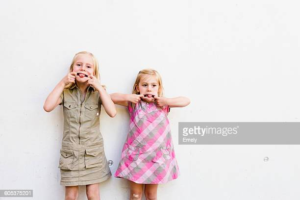 Portrait of two cute sisters pulling faces in front of white wall