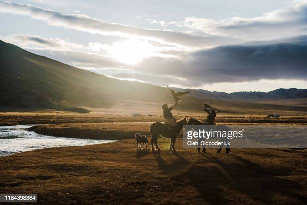 portrait of two eagle hunters near the river in mongolia - mongólia imagens e fotografias de stock