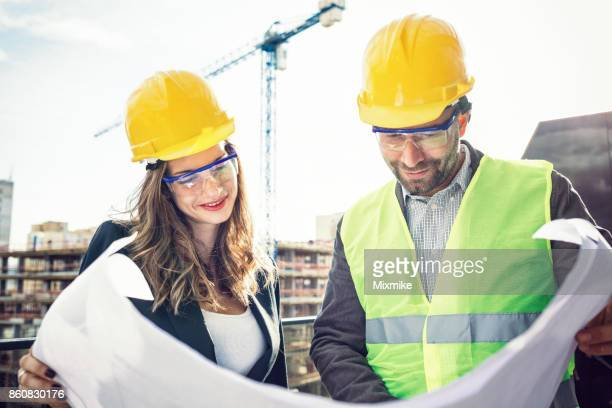 portrait of two engineers looking at a whiteprint plan - coordinazione foto e immagini stock