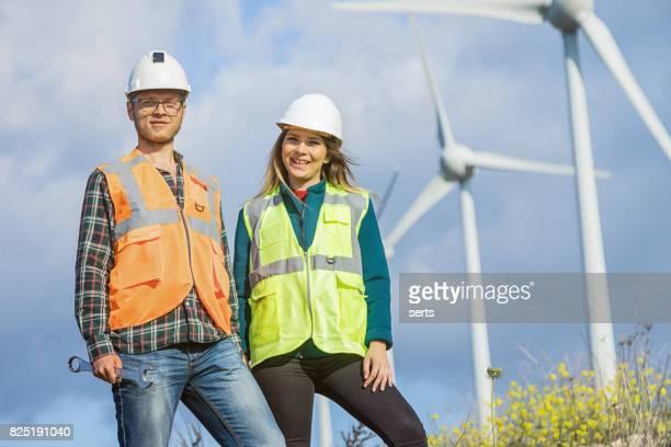 portret van twee ingenieurs poseren voor energie turbine windpark - vest stockfoto's en -beelden