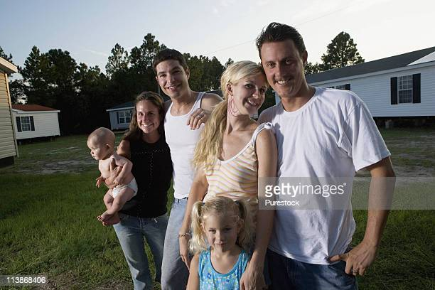 Portrait of two families standing in front of trailer homes