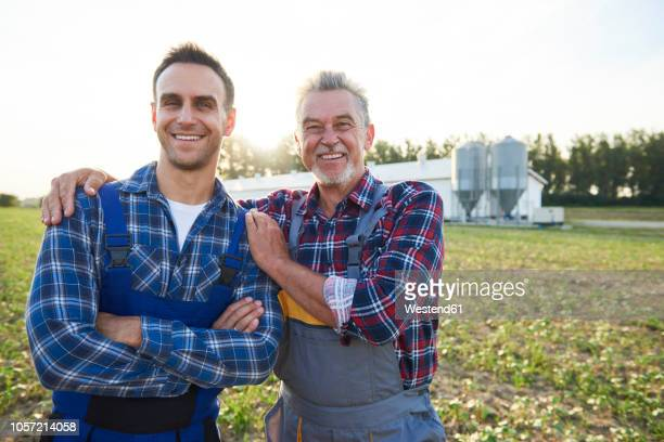 portrait of two farmers proud of their farm - two generation family stock pictures, royalty-free photos & images