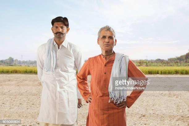 Portrait of two farmers standing in field