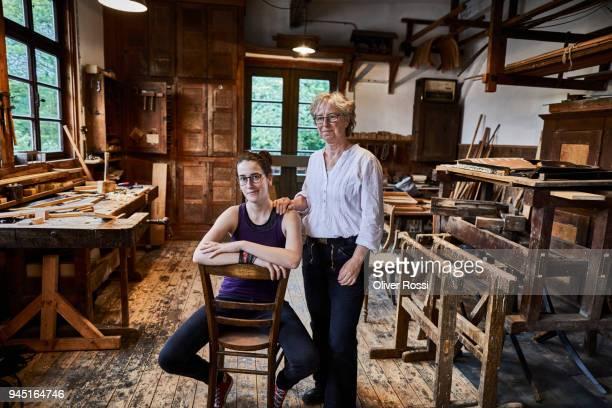 portrait of two female carpenters in workshop - 後任 ストックフォトと画像