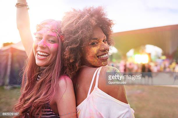 Portrait of two female friends at festival, covered in colourful powder paint