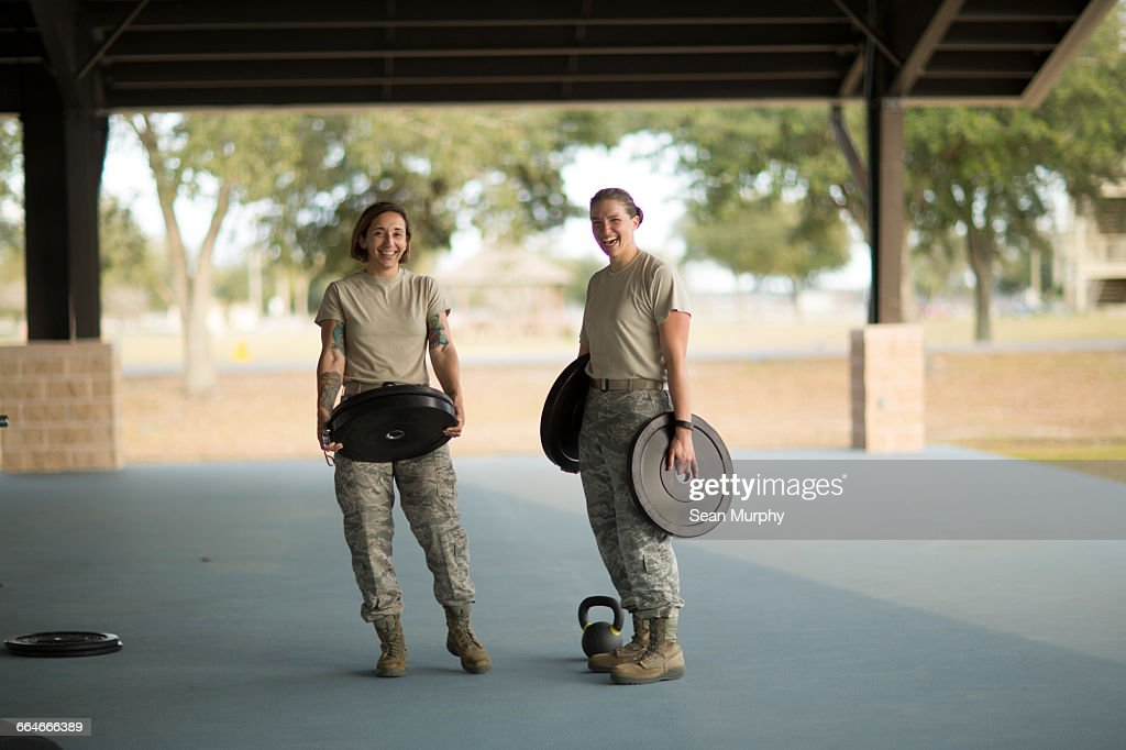 Portrait of two female soldiers barbell training at military air force base : Bildbanksbilder