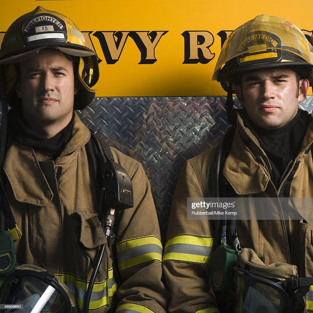Portrait of two firefighters sitting : Foto de stock
