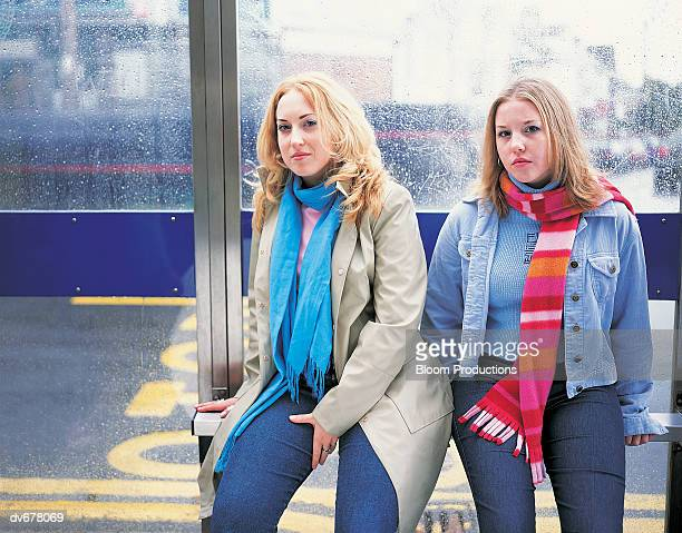 Portrait of Two Friends Sitting at a Bus Stop