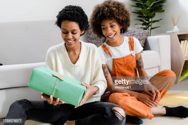 portrait of two friends sitting on the floor at home looking at gift - gift lounge stock-fotos und bilder