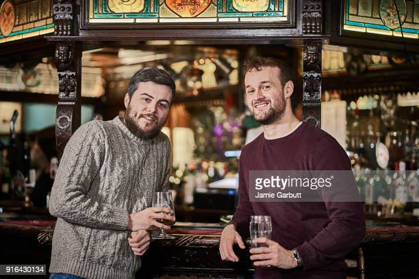 portrait of two friends stood at the bar of a traditional british pub smiling happily - pub stock pictures, royalty-free photos & images