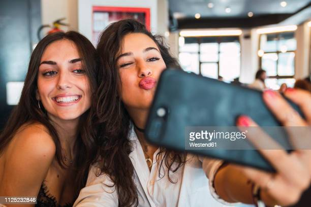 portrait of two friends taking selfie with smartphone in a coffee shop having fun - mulheres fotos imagens e fotografias de stock