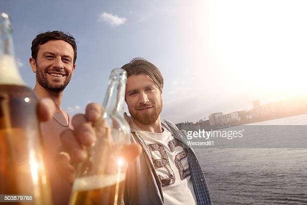 Portrait of two friends with beer bottles on riverbank