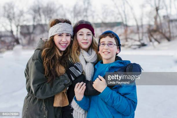 Portrait of two girls and a boy (sibling) on a ice rink at winter