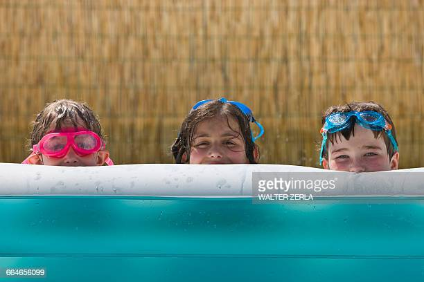 Portrait of two girls and boy peering from garden paddling pool