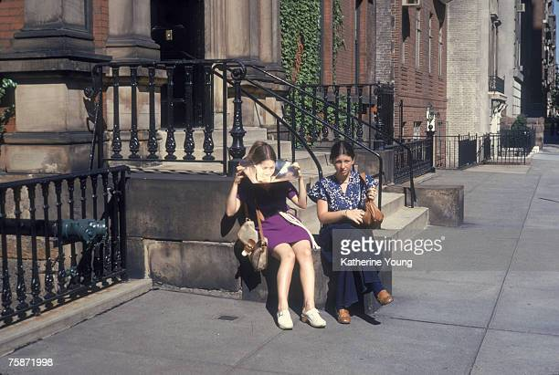 Portrait of two girls as they sit on the stoop of a house on 70th Street New York New York 1970s One holds a sun reflector under her chin