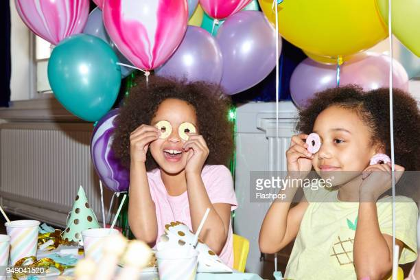 portrait of two girls at a party - birthday balloons stock photos and pictures
