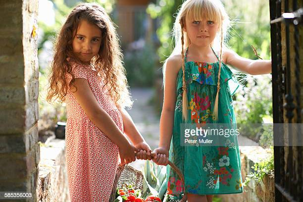 portrait of two girls holding basket of fresh tomatoes in garden - beautiful turkish girl stock pictures, royalty-free photos & images