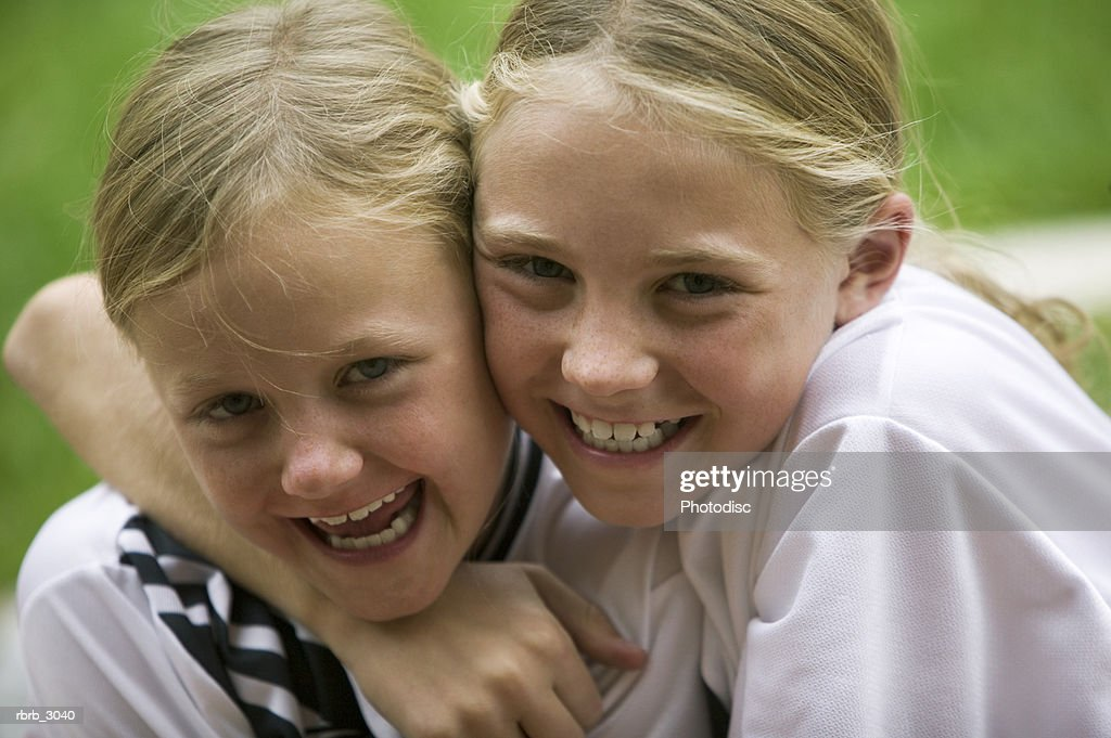 Portrait of two girls holding each other smiling : Foto de stock