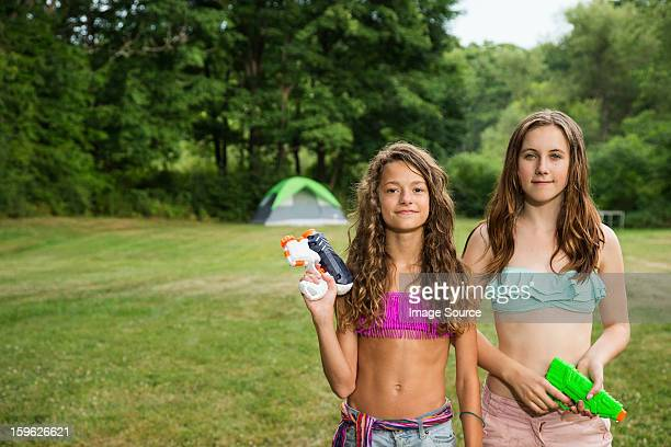 Portrait of two girls holding water pistols