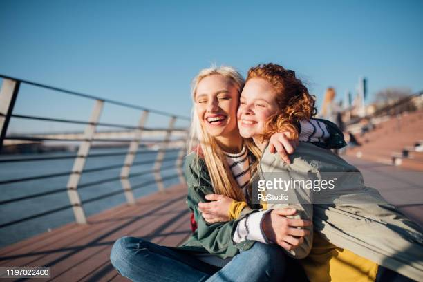 portrait of two girls hugging and enjoying the sun - girls of the sun stock pictures, royalty-free photos & images
