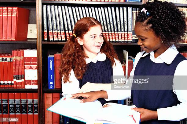portrait of two girls (8-10) reading together at the library - 10 11 jahre stock-fotos und bilder