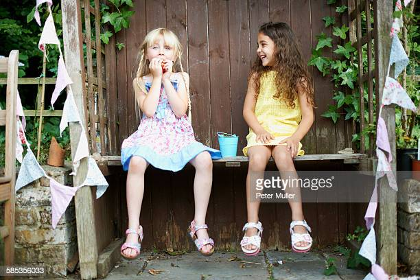 Portrait of two girls sitting on bench eating a bucket of fresh strawberries