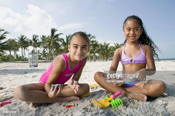 Portrait of two girls sitting on the beach and playing with sand