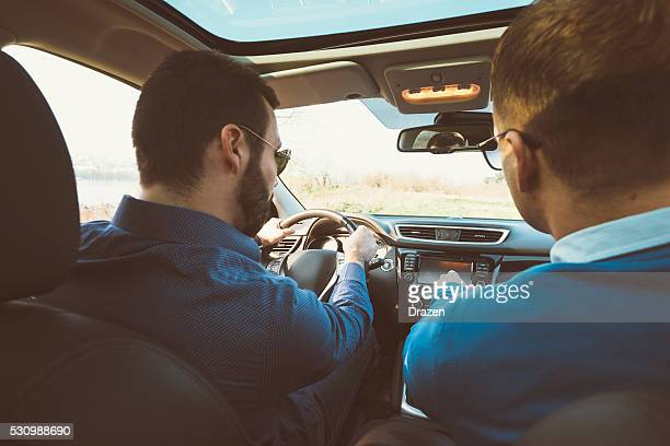 Portrait of two handsome men in car driving for holiday