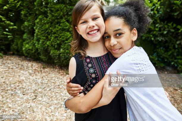 portrait of two happy girls hugging outdoors - linda oliver fotografías e imágenes de stock