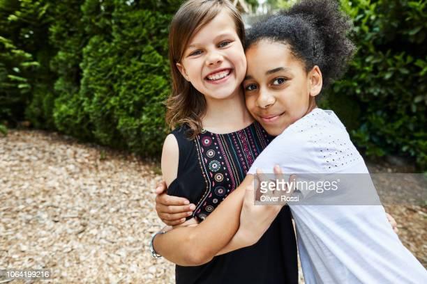 portrait of two happy girls hugging outdoors - multiculturalismo foto e immagini stock