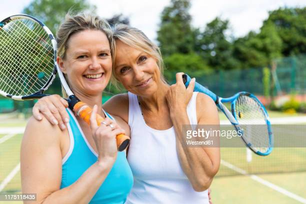 portrait of two happy mature women on grass court at tennis club - gras stock pictures, royalty-free photos & images