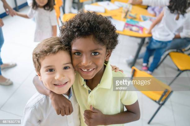 portrait of two happy multi-ethnic friends at school - male friendship stock pictures, royalty-free photos & images