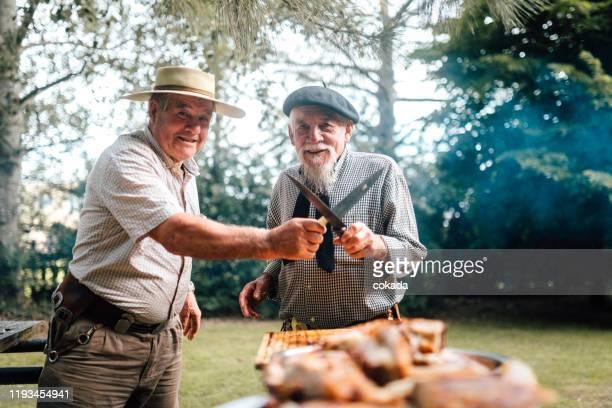 porträt von zwei glücklichen senior argentinischen gauchos bereiten traditionellen grill - argentinischer abstammung stock-fotos und bilder