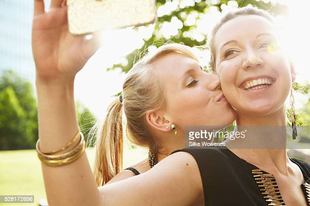 Portrait of two happy sisters having fun while taking self portrait with smartphone in park