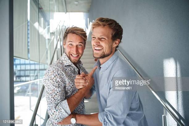 portrait of two happy young businessmen shaking hands - gründer stock-fotos und bilder