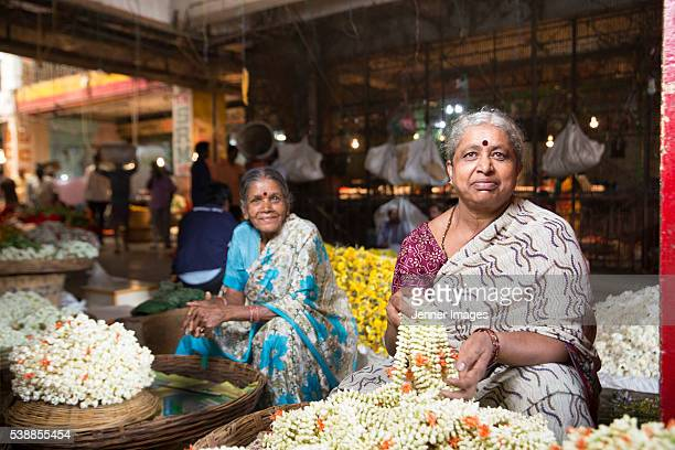 Portrait of two Indian women trader's at a city flower market.