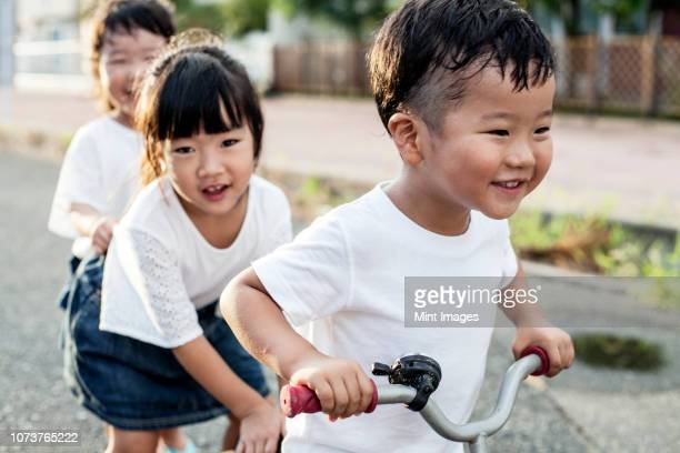 portrait of two japanese girls and boy playing on street with a bicycle, smiling at camera. - childhood photos ストックフォトと画像