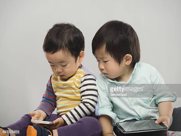 の肖像 2 つの日本のお子様には、お部屋の電子機器。 - 兄弟 ストックフォトと画像
