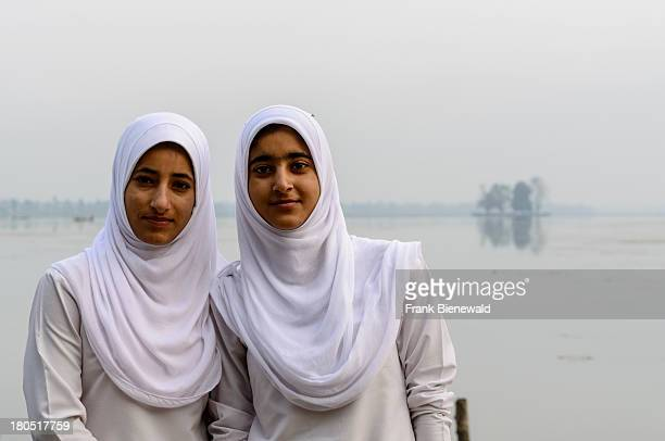SRINAGAR JAMMU KASHMIR INDIA A portrait of two Kashmiri school girls in their school dresses covering their heads with white shawls