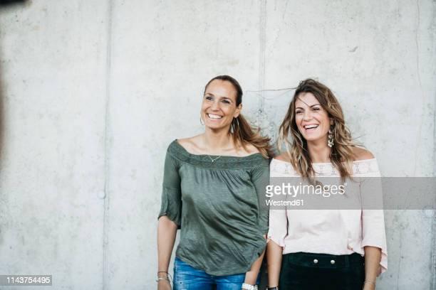 portrait of two laughing friends standing side by side - weibliche freundschaft stock-fotos und bilder