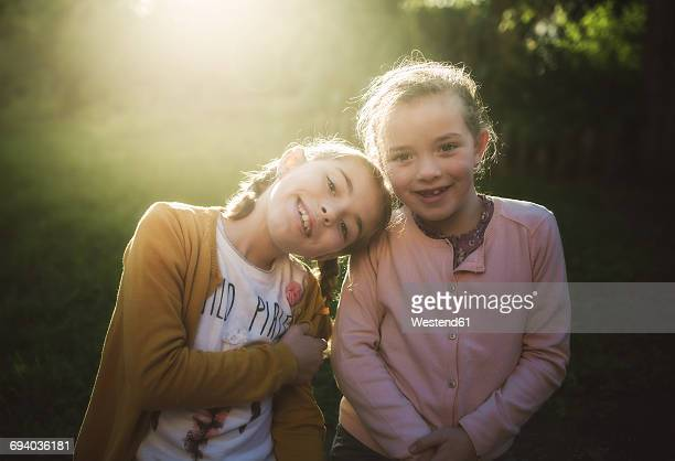 Portrait of two little girls at backlight