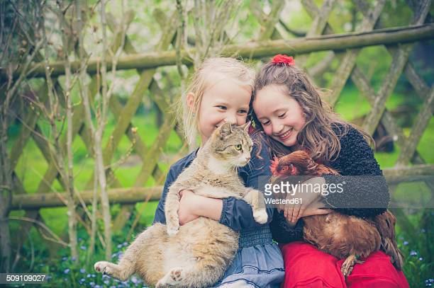 Portrait of two little girls with cat and chicken